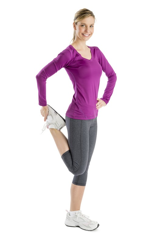 Full length portrait of happy young woman doing stretching exercise against white background