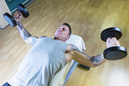 man making dumbbell fly - chest exercise - lying on a bench at the gym - start exercise - focus on the man face